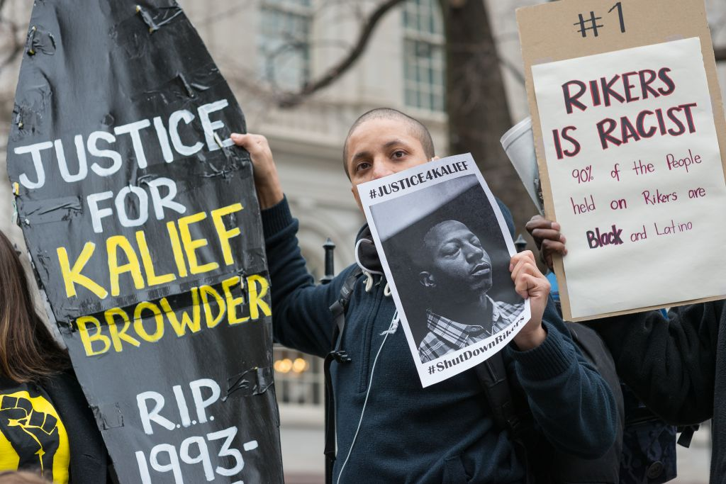 Demonstrators hold aloft a symbolic coffin bearing Kalief...
