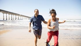 Playful couple running on sunny beach