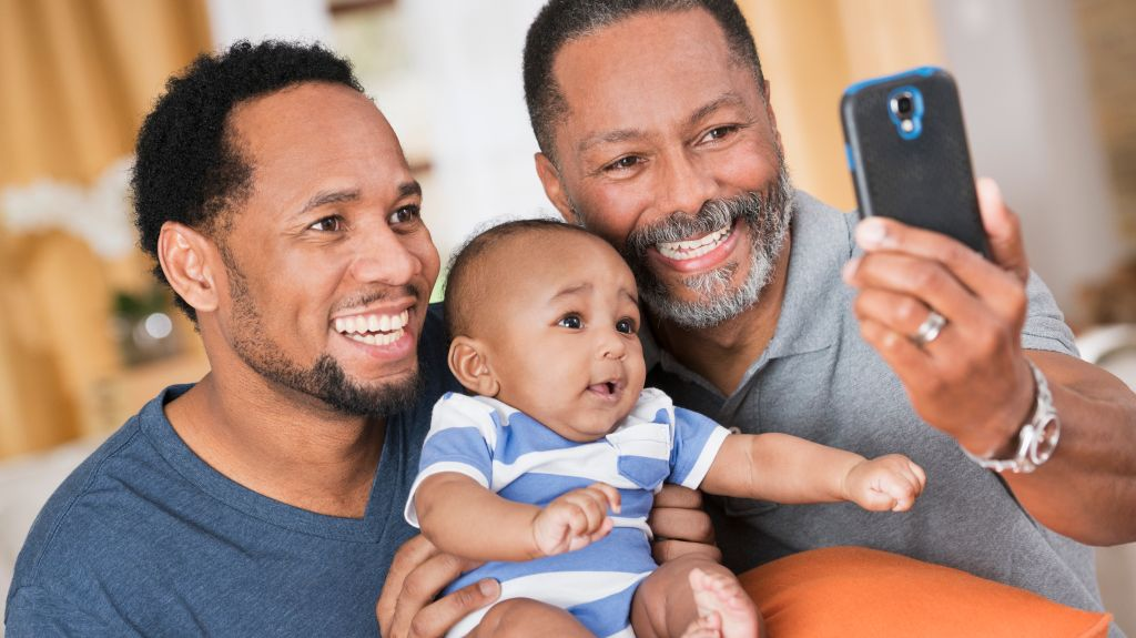 Black father and grandfather posing for cell phone selfie with baby boy