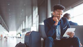 Young man at airport waiting lounge using digital tablet