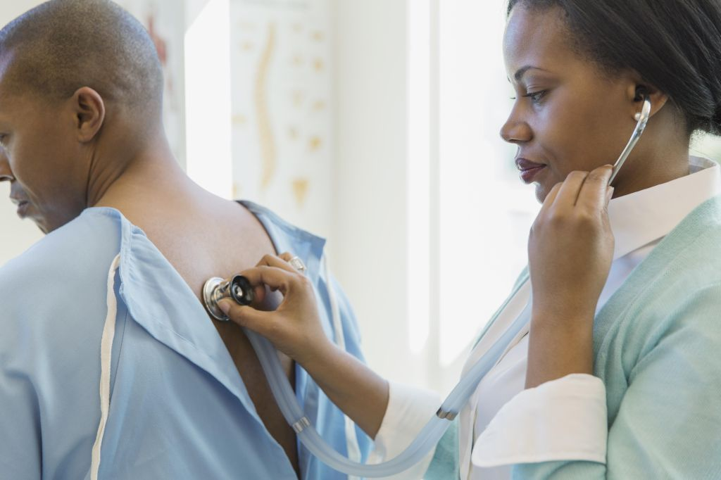 Female doctor using stethoscope on patient's back in clinic