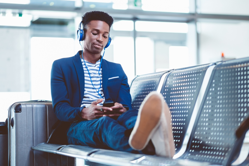 Young african man waiting for flight at airport lounge
