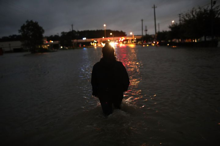 A Houston resident walks through waist-deep flood water as she evacuates her home.