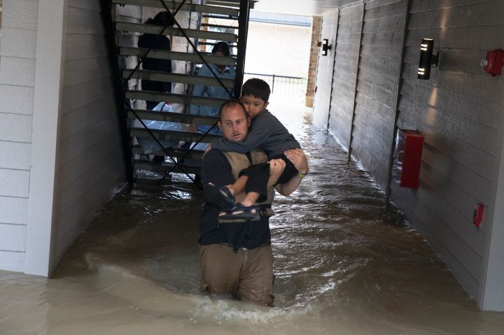 Police and volunteers rescue residents flooded by the San Jacinto river in Kingwood, Tex.