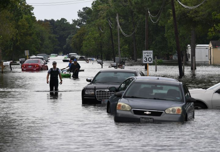 Crosby, Tex. residents wade through flooded streets.