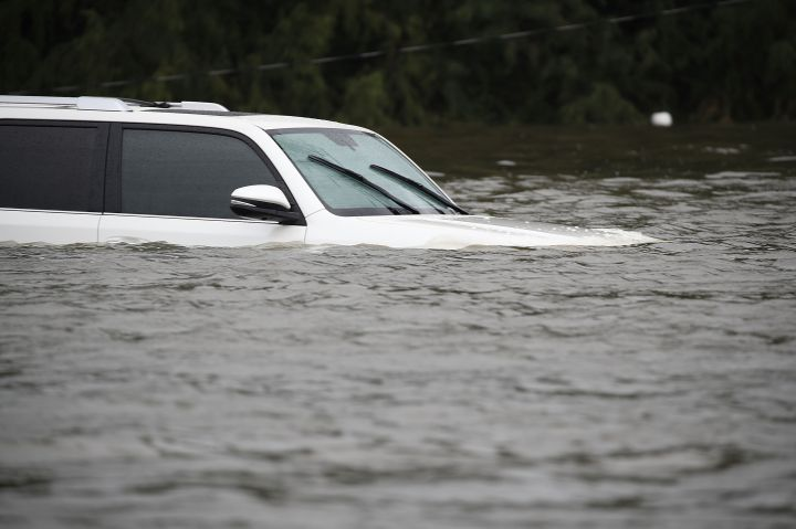 An SUV is submerged in flood water.