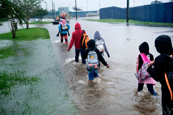 Young kids escape a flooded neighborhood.