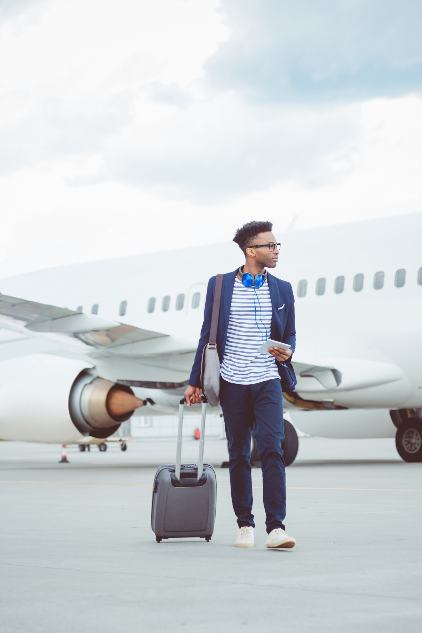 Young african businessman walking in front of airplane