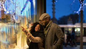 Couple window shopping in city at night, New York, USA
