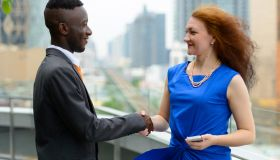 Portrait of young African businessman and young businesswoman together against view of the city in Bangkok Thailand