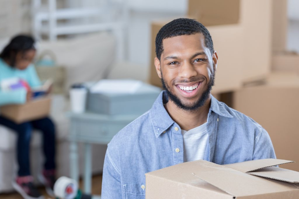 Young man smiles for camera while holding moving box