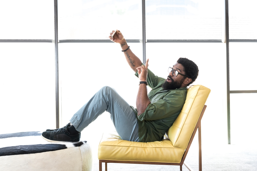Black man sitting in chair posing for cell phone selfie