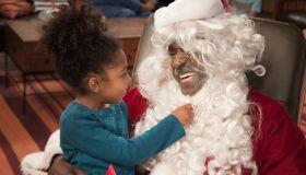 Girl pulling on Santa's beard