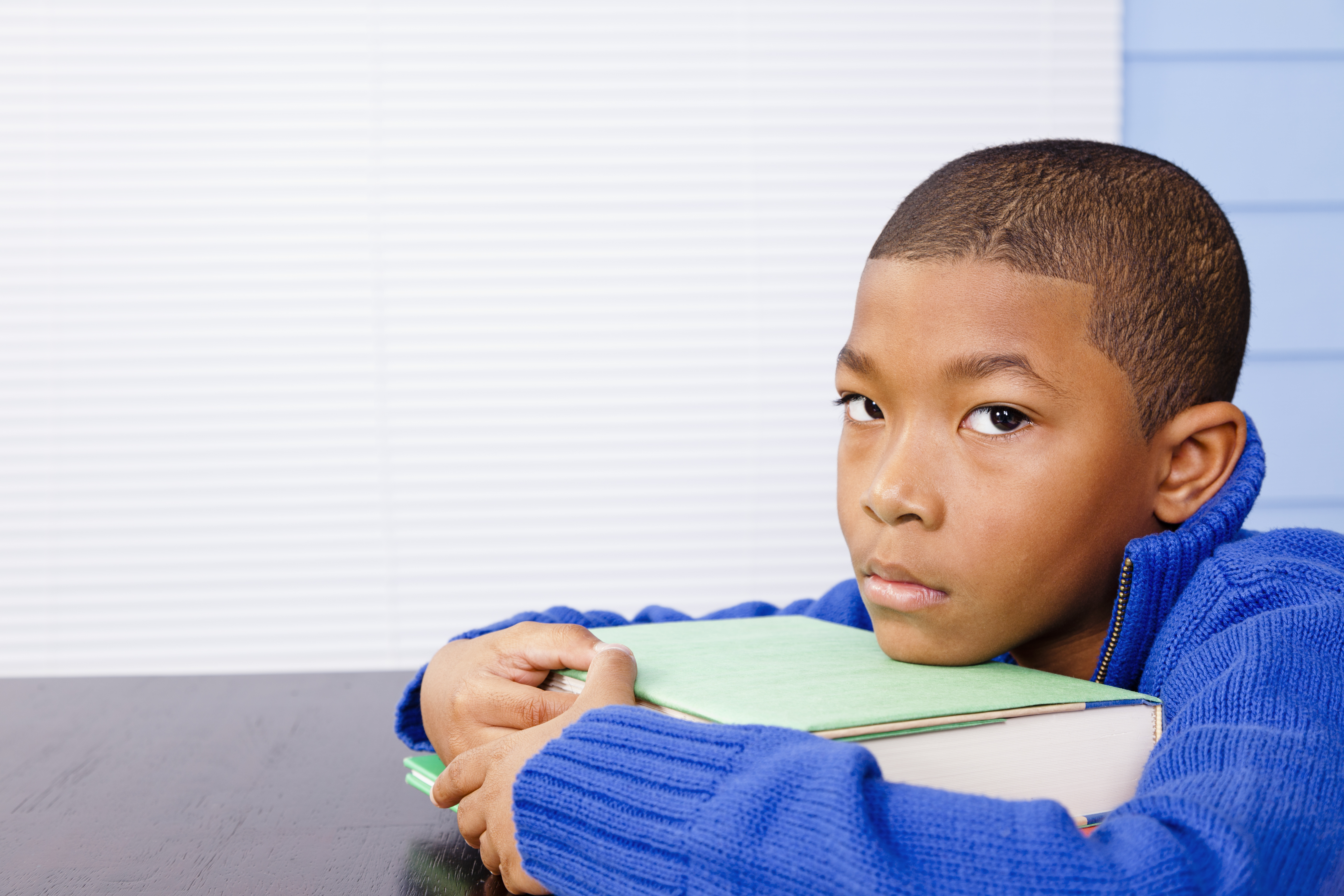 Young elementary aged boy procrastinating homework or depressed