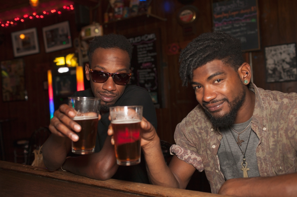 Two young men toasting at a bar.