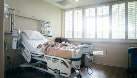 Empty hospital bed near sunny window