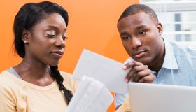 Young black couple paying bills at home