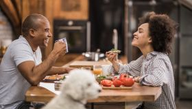 Happy black couple enjoying in conversation during breakfast time in the kitchen.