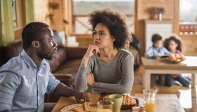 African American couple talking during breakfast time at home.