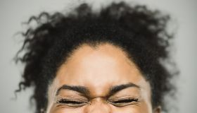 Excited happy afro american woman against gray background