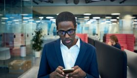 Modern African-American Businessman Using Phone in Office