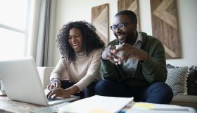 Laughing couple with laptop drinking coffee and paying bills online in living room