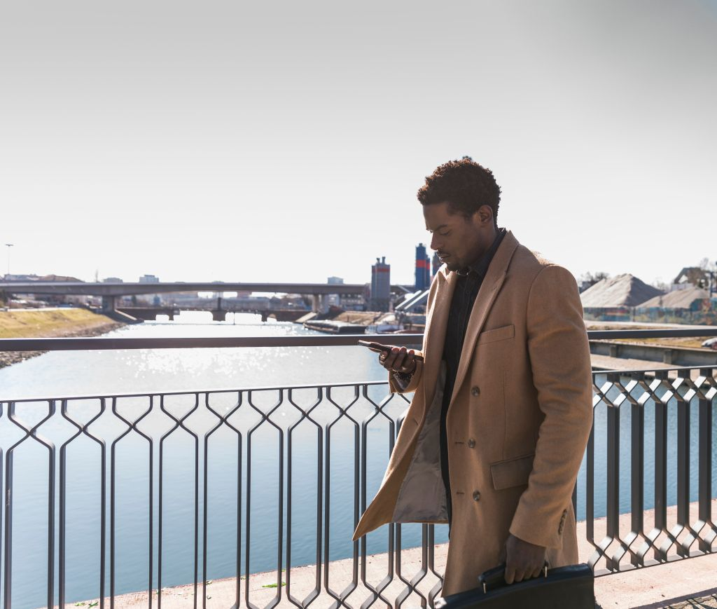 Businessman walking on a bridge with cell phone and briefcase