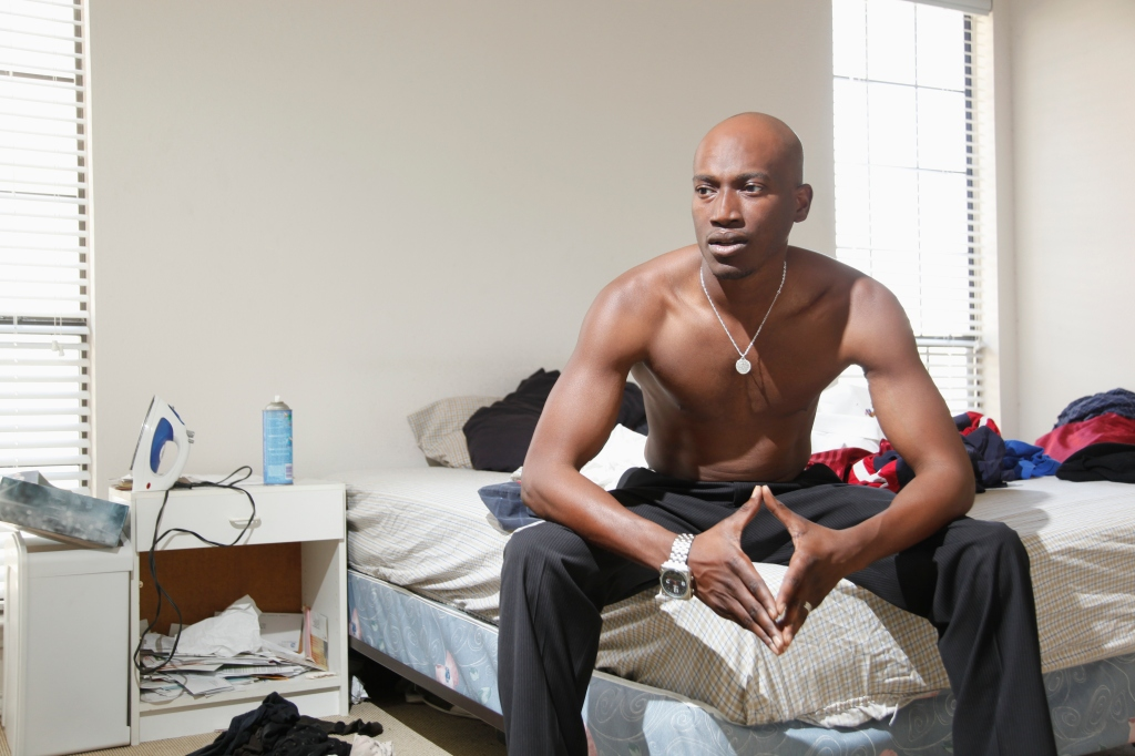 Serious African American man sitting on bed