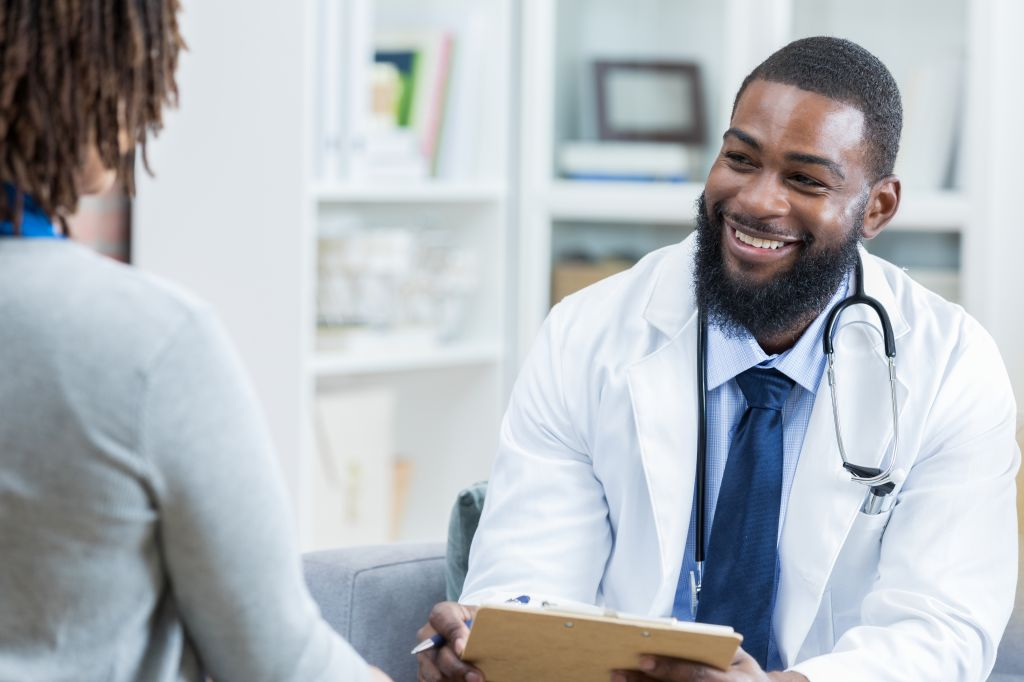 Physician takes notes while talking with patient
