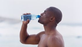 Side profile of a young man drinking water from a bottle