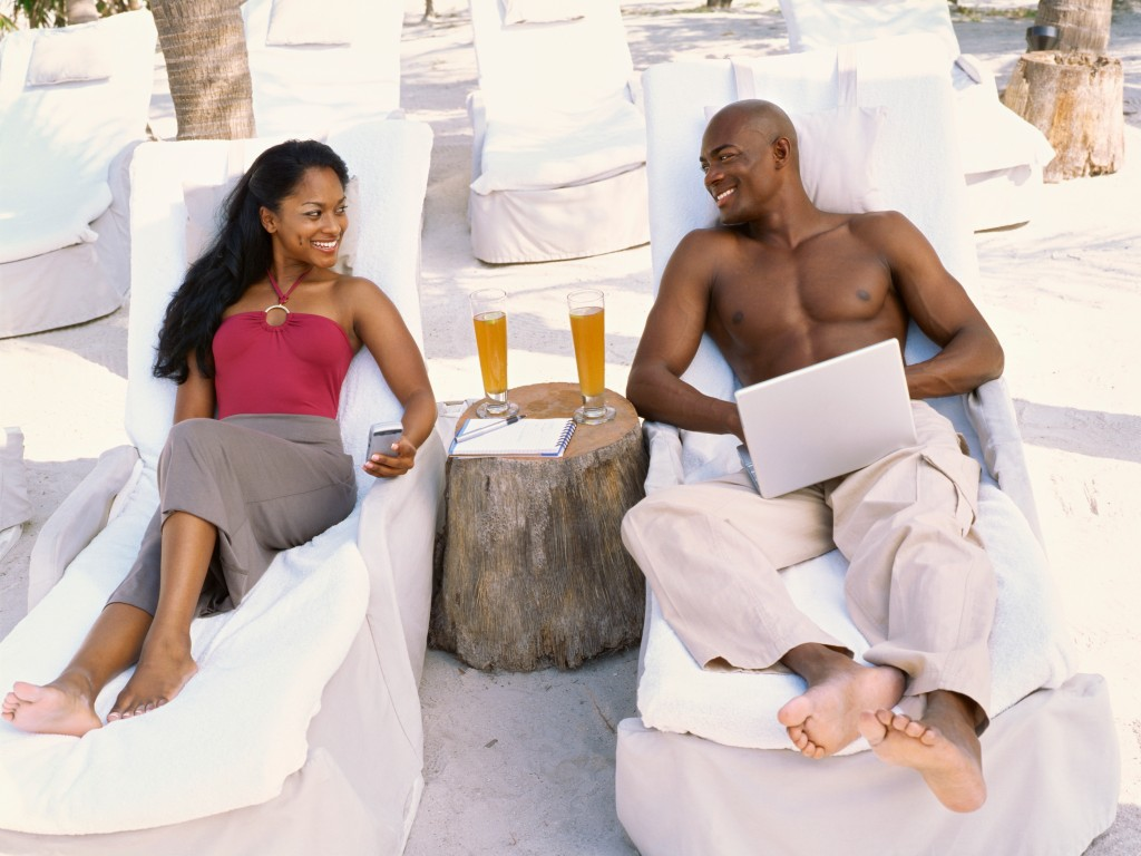 Young couple sitting on loungers and looking at each other