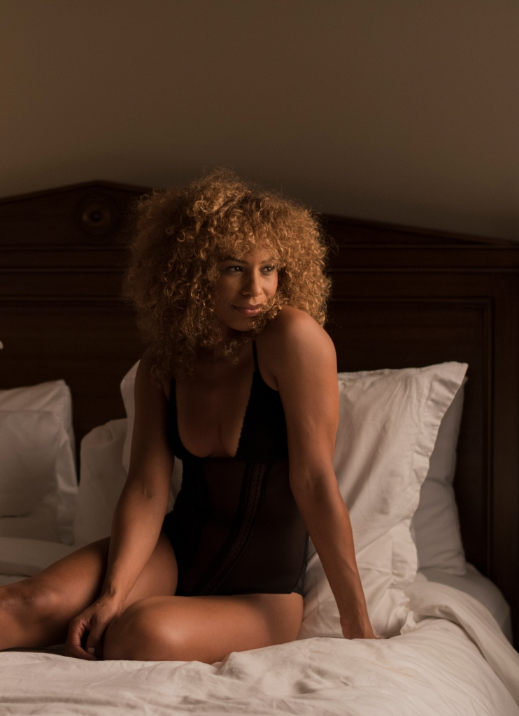 Mixed Race Woman Wearing Lingerie Sitting on a Bed