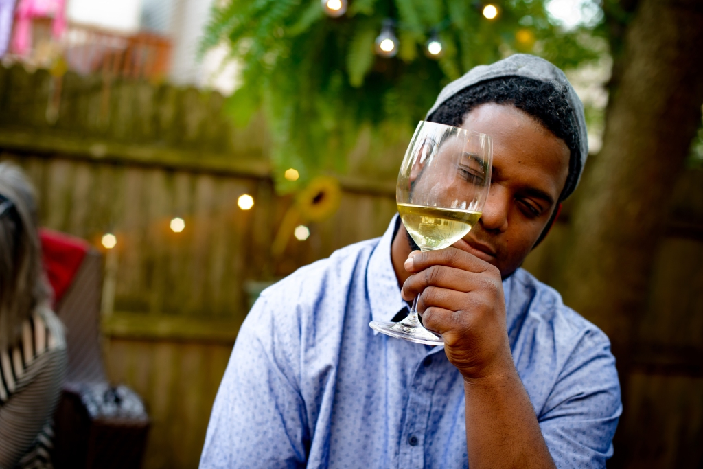 Man at garden party, holding wine glass, inspecting wine