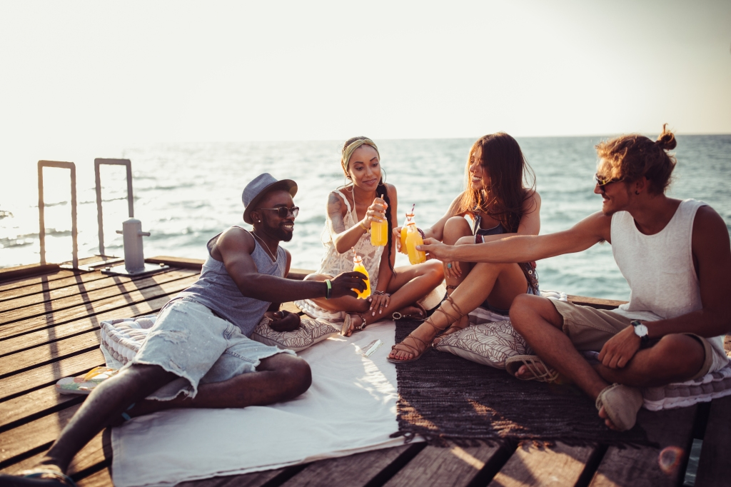 Multi-ethnic friends drinking soda and having beach party on jetty