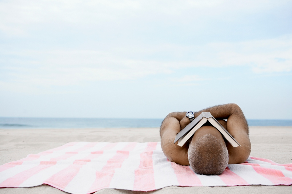 Man sleeping on beach with book on his face