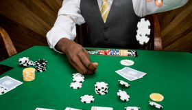 Man dropping poker chips on table