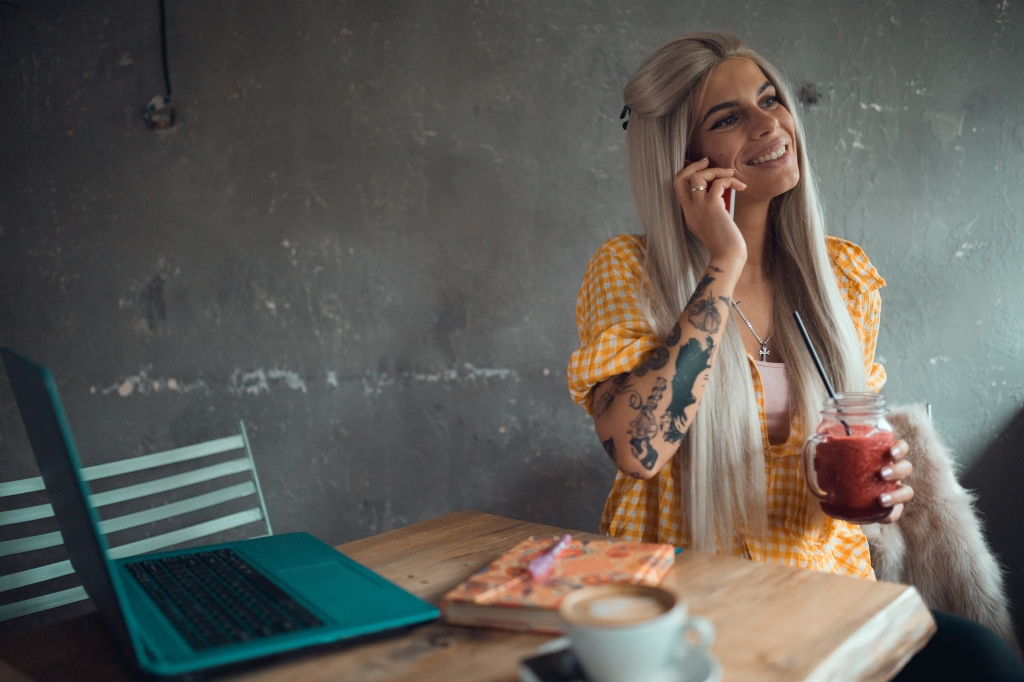 Smiling young woman using phone inside the coffee bar