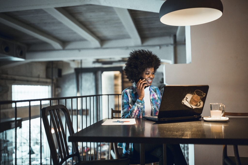 Young woman, African-American Ethnicity, working at laptop in cafe, using mobile phone.