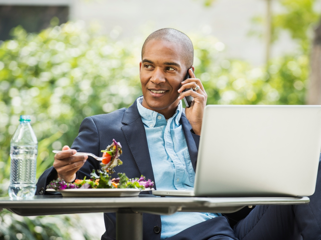 Black businessman working and eating lunch outdoors