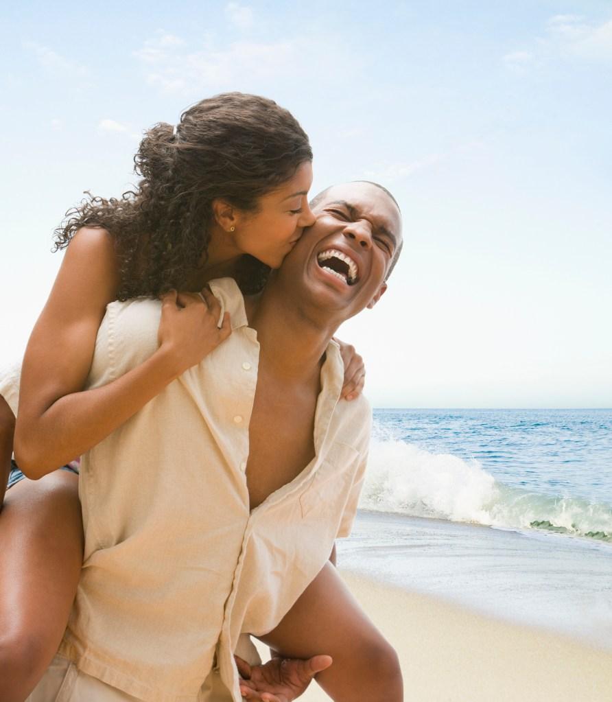 African American man giving girlfriend piggyback ride