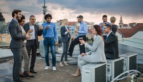 Large group of happy business colleagues talking on a rooftop party.