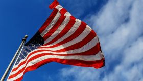 Low Angle View Of American Flag Waving Against Sky