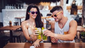 Young hipster couple toasting with cocktails at island summer bar