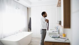 Man putting on tie at mirror in morning bathroom
