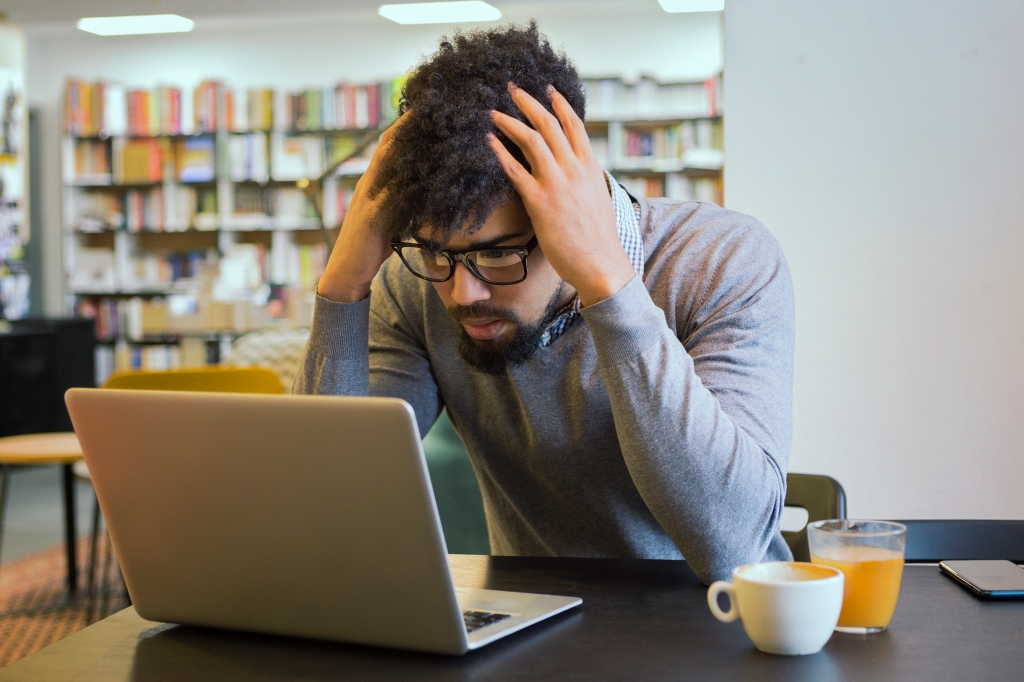 Young student getting frustrated over laptop in library