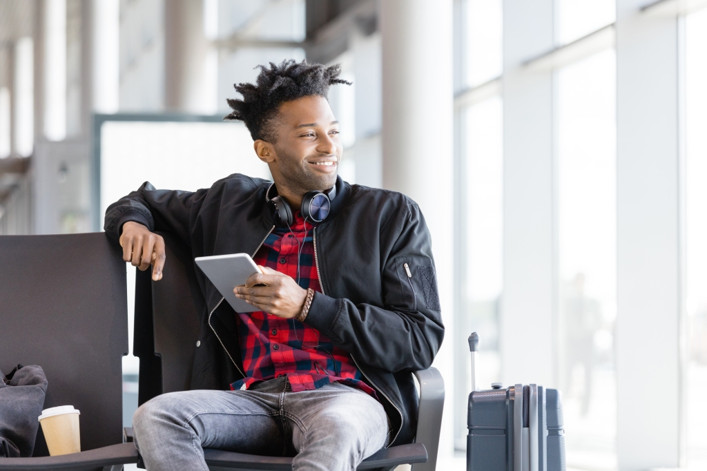 Young african using digital tablet in airport lounge