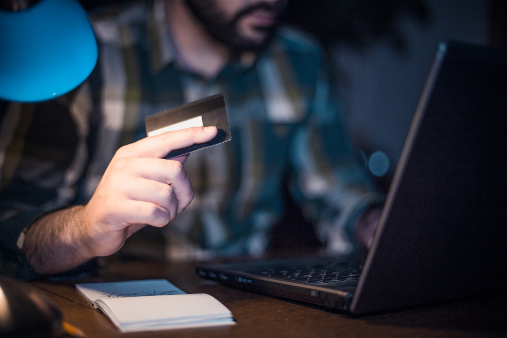 Close-up of a man using credit card to shop from home