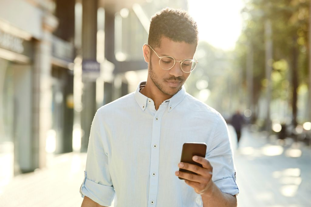 Young man using mobile phone on sidewalk in city