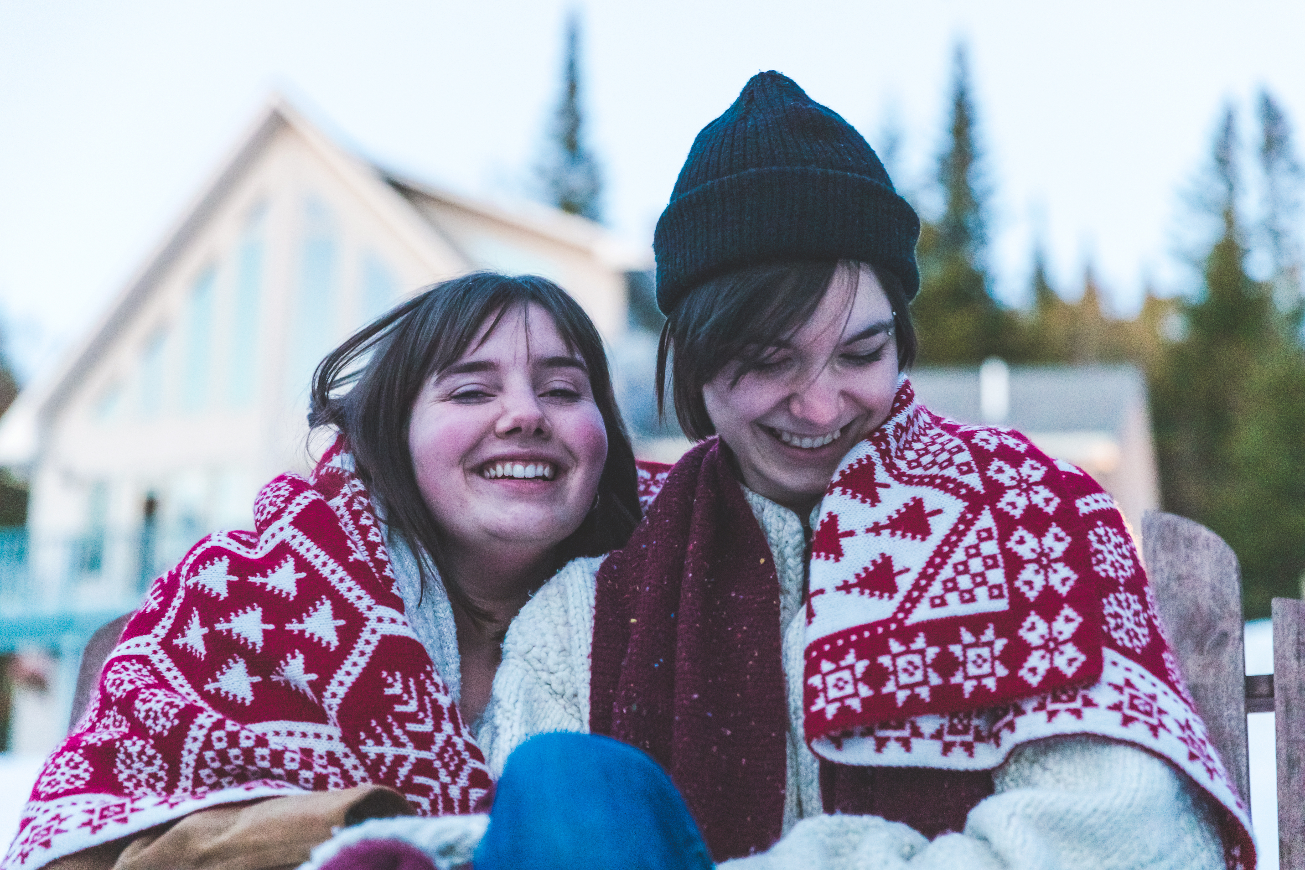 Lesbian Couple Wrapped in the Warm Blanket sitting outside their Holiday Villa