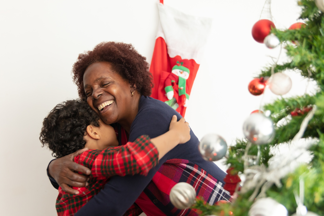 Loving grandmother and grandson hugging very cheerfully standing next to the christmas tree